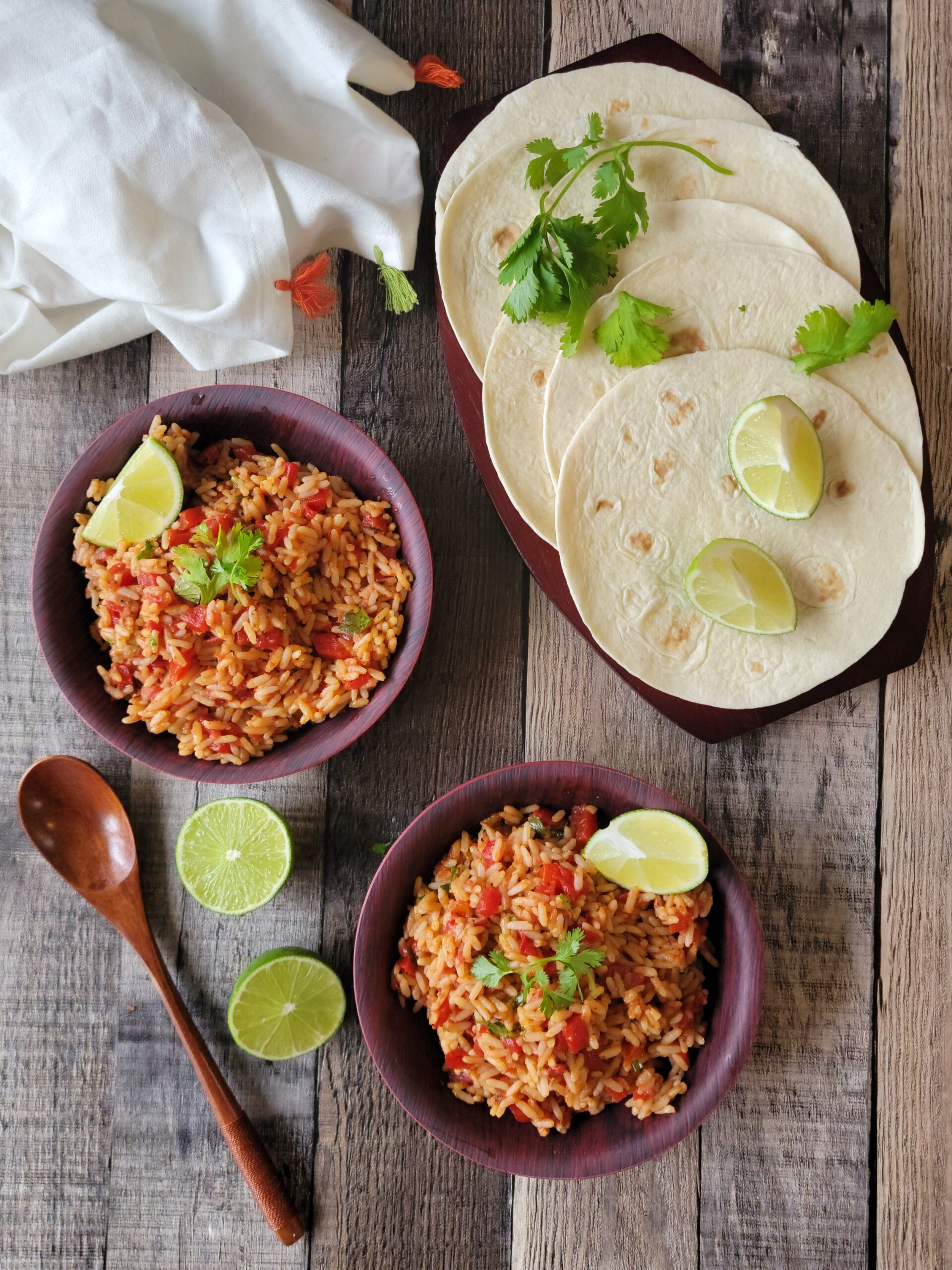 A table laid with Fire Roasted Mexican Rice, limes and tortillas